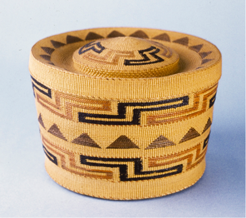"Tlingit Rattle-Top Basket (0840-0045AB)  This spruce root basket displays examples of linear and rotational symmetry on its side, lid and bottom. The final type of symmetry - point - can also be seen on the side of the basket. The ""s"" and ""z""-shaped design is called the ""shaman's hat"", and the bands on the top and bottom face opposite directions. A black ""z"" that is diagonal from a black ""s"" could be flipped up and over an imaginary point between those two figures to lie perfectly on top of that black ""s""."